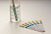 close up of ph analysis strips with a strip inserted in a graduated tube with water, on a rough metallic surface