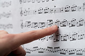 Female finger following the notes on a music score