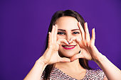 Happy woman shows heart sign on purple background