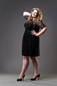 Plus size fashion model in black dress, fat woman on gray background