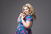 Plus size fashion model in floral dress, fat woman on gray background