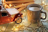 Christmas festive background.Winter books.Winter cozy reading.A stack of books, a mug of tea, a shining garland and a red decorative car on a light blue wooden background.Winter comfort