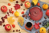 autumn tea.Thanksgiving Day. Red teapot, a cup of tea, apples,pumpkin, chestnuts and autumn leaves on a light wooden table.Autumn cozy mood.Fall season