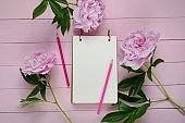 Peony flowers. Spring Flat Lay.Floral mockup.Spring To Do List.Blank notebook, pink peony flowers and pink pencils on a pink wooden background. spring floral background in pink colors.