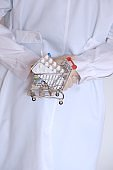 Medicine and health . Buying and selling drugs. Treatment of viral diseases.A doctor in a white coat holds a supermarket trolley with medicines behind his back.Painkillers and antibiotics pills