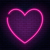Neon sign in heart shape. Glowing neon heart on brick wall background. Neon signboard, love concept