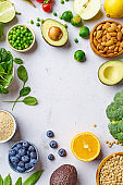 Creative flat lay with healthy vegetarian meal ingredients. Raw food concept. A variety of organic fruits, nuts, berries and vegetables with avocado. Vegan menu frame with copy space