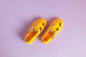 Bright yellow baby shoes on a lilac background with copyspace. Baby clothes concept.