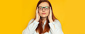 Worker young woman in shirt and eyesight glasses with headache on yellow wall background. Stress, fatigue people concept. Hold hands on head