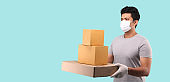 Handsome Asian man wearing face mask to protect from germ and virus. holding with parcel post box in cardboard boxes on light blue background in studio With copy space.