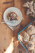 Freshly baked cinnabon buns with butter cream in a glass dish on a wooden table, top view flat lay