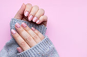 Female hands in a gray knitted sweater with trendy beautiful manicure - pink nude nails with black small dots on a pink background with copy space