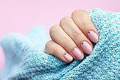 Female hand in a blue knitted sweater fabric with trendy beautiful manicure - pink nude nails with black small dots on a pink background with copy space