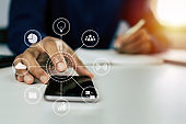 man hand working about financial on mobile phone with virtual digital icon and writing report on desk at home office, digital marketing, work from home, business finance, network technology concept