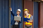 industrial worker caucasian woman and asian engineer control worker checking cargo container at container cargo harbor, transport, industrial, logistic, transportation, import and export concept