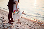 Bride and groom kiss near sea