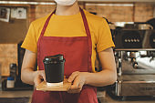 friendly waitress woman wearing protection face mask waiting for serving hot coffee cup to customer in cafe coffee shop, cafe restaurant, service mind, new normal, food and drink delivery concept