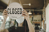 Closed. waitress woman wearing protection face mask turning close sign board on glass door in modern cafe coffee shop, cafe restaurant, retail store, small business owner, food and drink concept