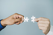 Partnership. two businessman partner teamwork trying to connect couple puzzle piece for matching to goal target success together, business strategy, marketing, association connection, partner concept