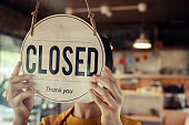 barista, waitress woman wearing protection face mask turning close sign board on glass door in modern cafe coffee shop, cafe restaurant, retail store, small business owner, food and drink concept