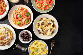 Italian pasta, various dishes, with meat, chicken, vegetables, mushrooms, seafood, shot from the top on a black background