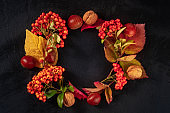 Autumn wreath with chestnuts and autumn leaves, shot from the top with copy space