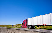 Burgundy big rig powerful semi truck with dry van semi trailer moving on the narrow road for delivery carried cargo