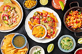Mexican food, a flat lay overhead shot on a dark background. Nachos, tacos, guacamole, shrimps, Paloma cocktails, shot from above