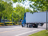 Blue day cab big rig semi truck with roof spoiler transporting cargo in dry van semi trailer turning on the green city street road