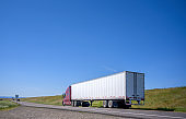 Dark red big rig semi truck transporting commercial cargo in dry van semi trailer driving on the narrow road with hill on the side