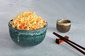 Instant noodles bowl with carrot and scallions, with chopsticks and sake, vegetable soba bowl with a place for text