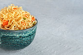 Instant noodles with carrot and scallions, vegetable soba bowl closeup with a place for text