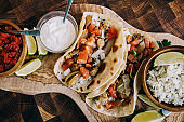 An olive board filled with delicious mexican fiesta of food tacos and burritos with cheese, onions, chicken, pico de gallo, cilantro lime rice and sour cream