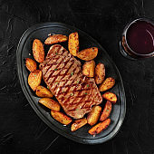 Grilled beef steak with baked potato wedges, with a glass of wine, square overhead shot on a dark background
