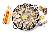 A dozen of oysters with wine and lemons, shot from above on a white background, a flat lay