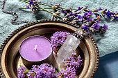Aromatherapy and flowers close-up. Scented candle and perfume vial with verbena and lavender flowers