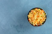 Instant noodles with carrot, scallions, and a sauce, a vegetable soba bowl, shot from the top with a place for text