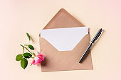 Invitation or greeting card mockup in a brown craft envelope, shot from above on a pink pastel background