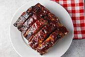 Oven baked barbecue ribs with sauce on a white plate with a red checkered picnic napkin