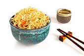 Instant noodles bowl with carrot and scallions, vegetable soba with chopsticks and sake, on a white background