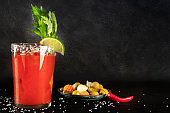 Bloody Mary cocktail with tomato juice, lime, and celery, wiuth pickles and a chili pepper, side view on a black background with copy space