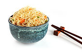 Instant noodles bowl with carrot and scallions, with chopsticks, on a white background