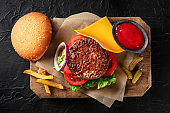 Burger with beef, cheese, onion, tomato, and green salad, with a bun and ketchup, with French fries, shot from above