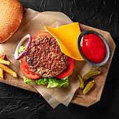 Burger with beef, cheese, onion, tomato, and green salad, with a bun and ketchup, overhead square shot on a black background