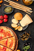 Italian antipasti and pizza, shot from above on a black background. Scamorza, parmesan, grissini, pesto, capers, olives