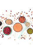 Legumes, overhead shot on a white background. Vibrant pulses including red beans, lentils, chickpeas, soybeans and black-eyed peas, a flat lay composition