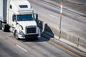 Big rig white semi truck with dry van semi trailer running on divided highway at sunny day
