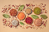 Legumes assortment, shot from the top on a brown background. Lentils, soybeans, chickpeas, red kidney beans, black-eyed peas, a vatiety of pulses
