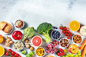 Vegetarian food products variety, overhead shot with copy space. Fruit, vegetables, cheese, mushrooms, nuts, legumes, a flat lay