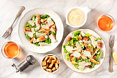 Caesar salad with the classic sauce and wine, shot from the top on a white marble background